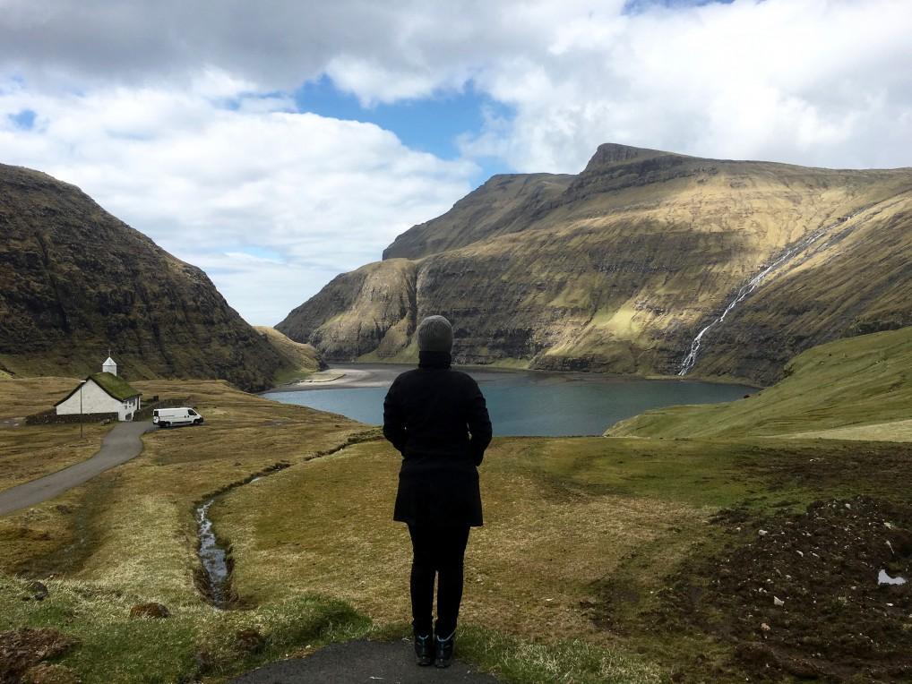 Saksun person som ser ut over fjell og fjord