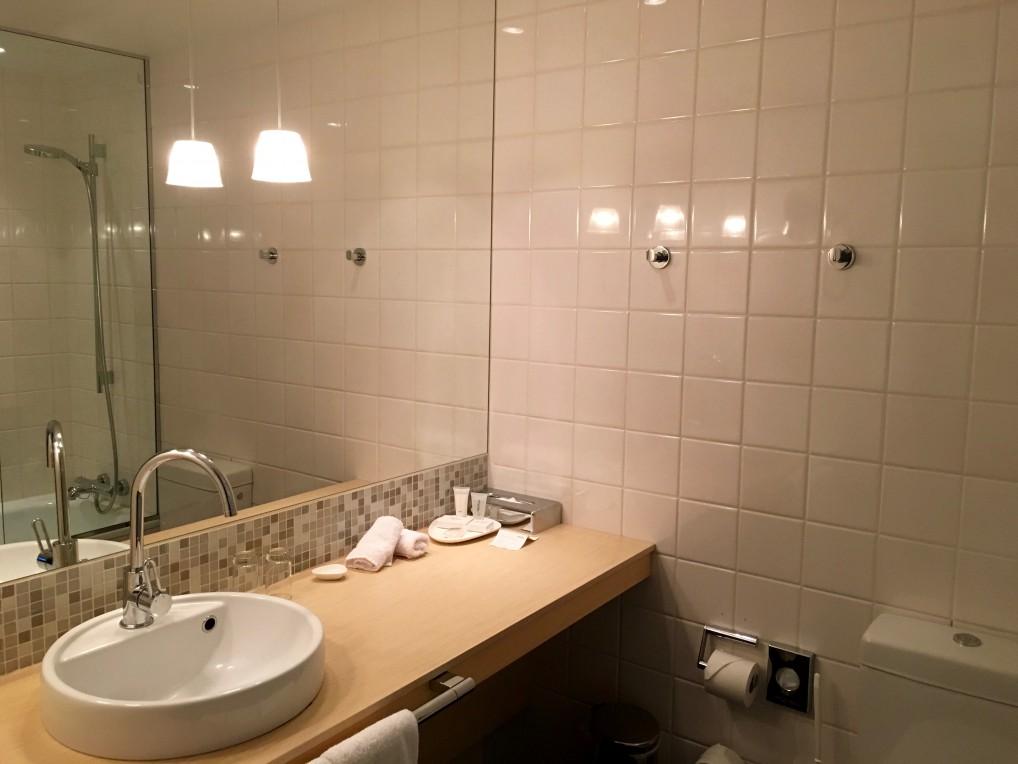 Bad med fliser og varmekabler og badekar